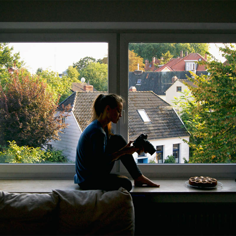 Woman sitting on window ledge with a camera, brighter view of roofs behind.