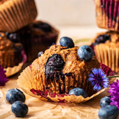 One muffin with paper removed, more stacked in background, with berries around.