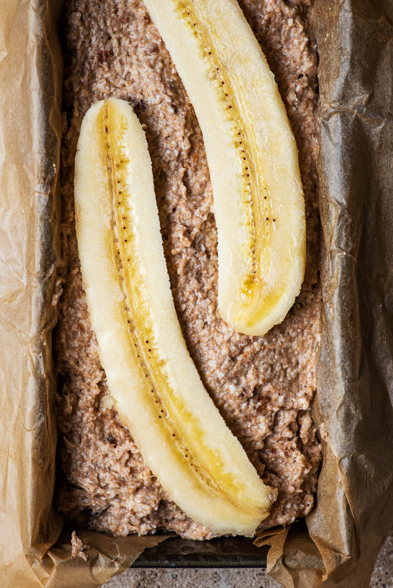 Batter added to a lined baking dish and topped with a halved banana.