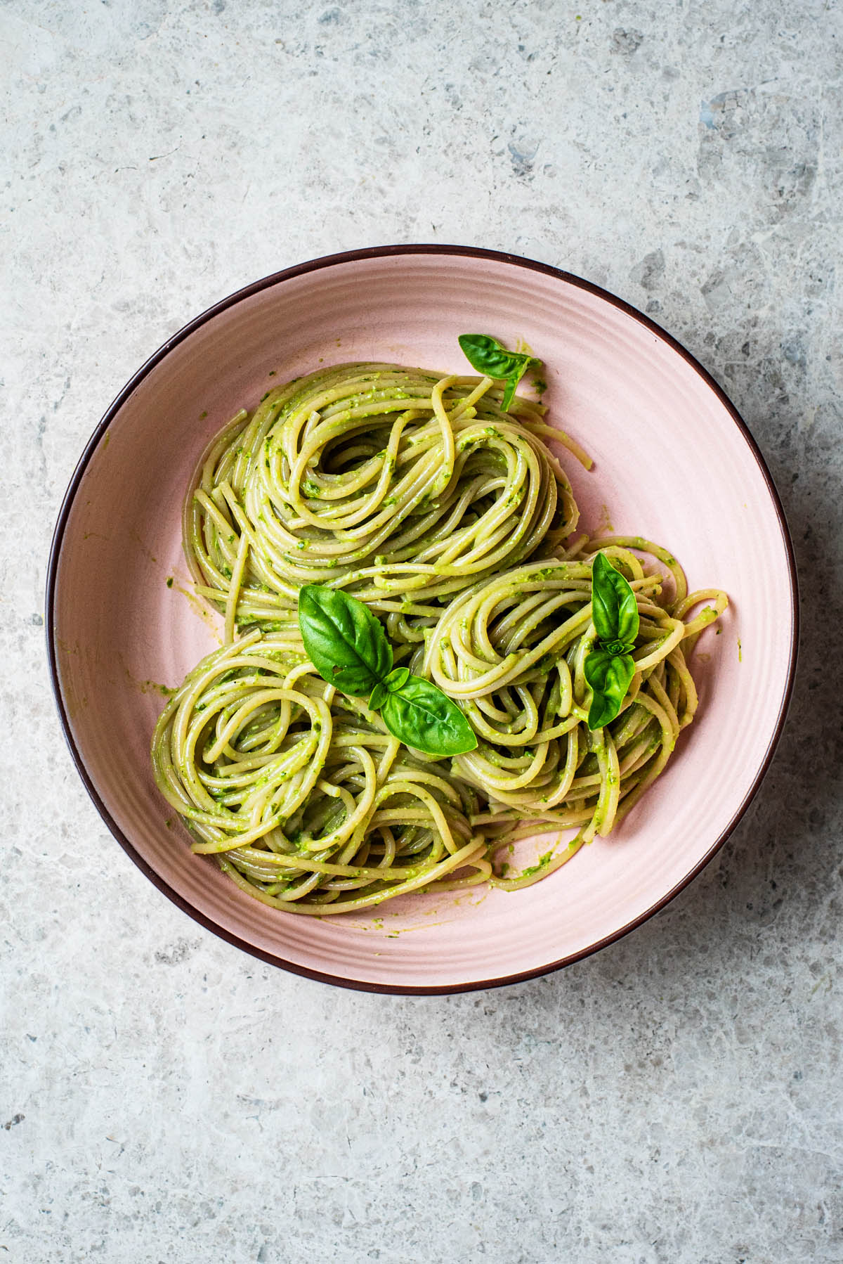 Spaghetti in a shallow bowl with pesto and basil leaves.