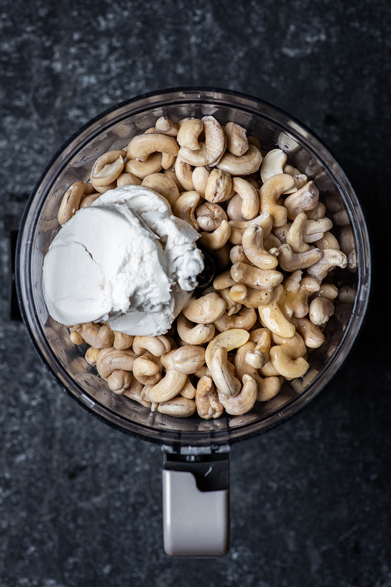 Cashews, coconut cream, maple syrup, and vanilla added to the mixer.