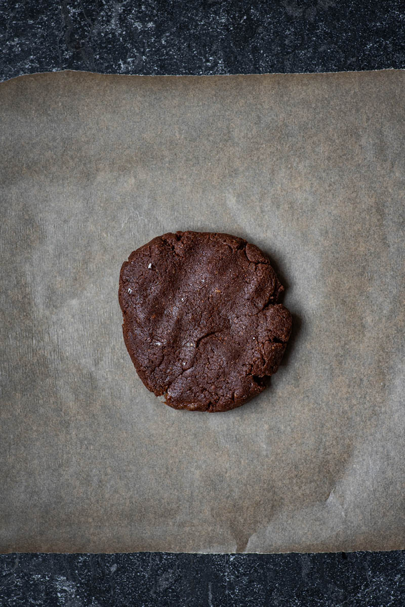 Half of the brownie base pressed onto parchment paper.