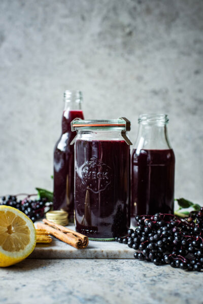 Three glass containers of dark purple elderberry syrup.