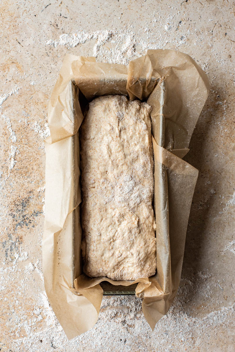 Shaped bread placed into a parchment lined baking tin.