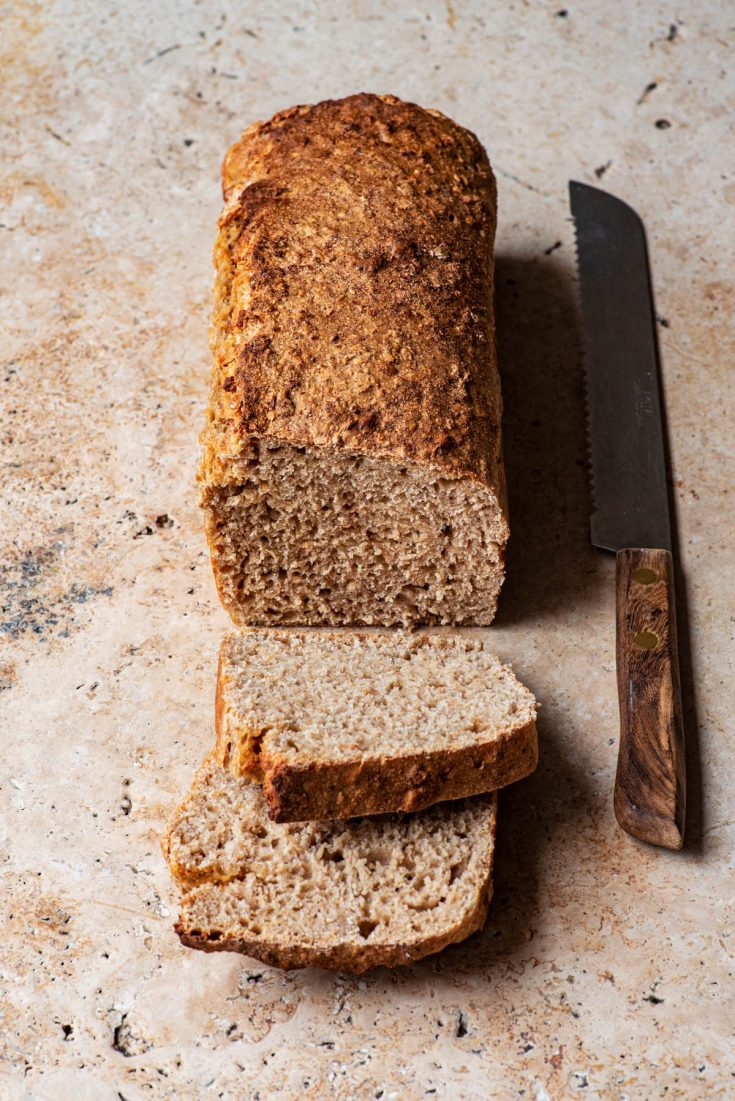 A loaf of bread with two slices cut and a knife alongside.