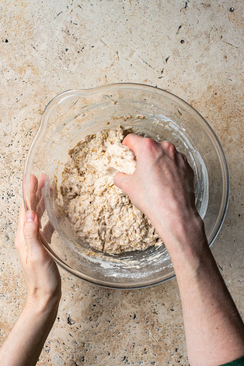 Hands reaching into the bowl to stretch the dough.