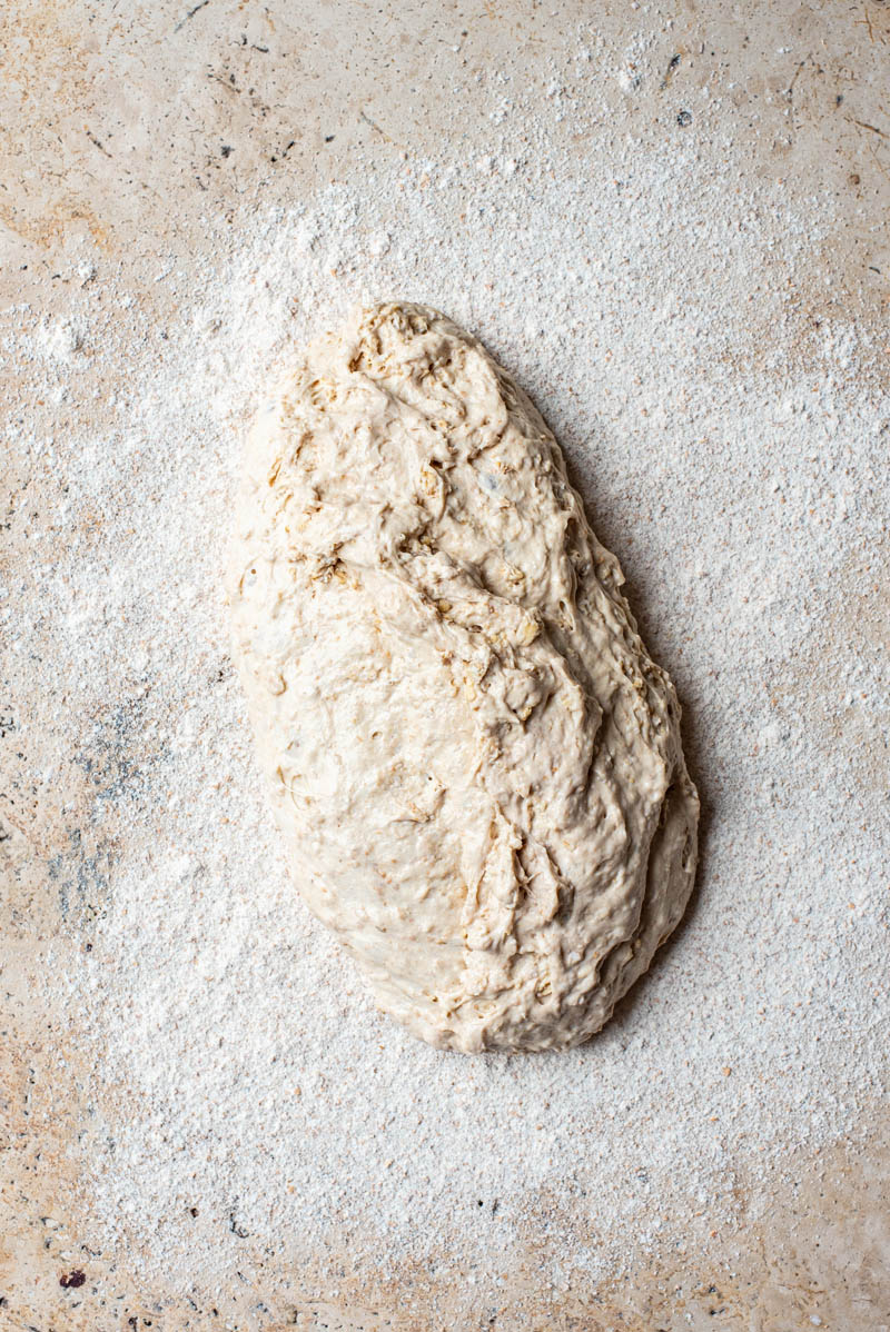 Fermented sourdough tipped out onto a floured surface.