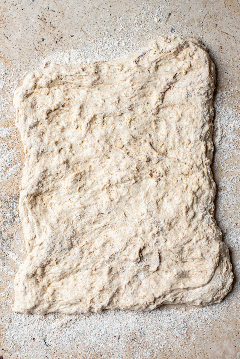 Dough pressed out into a rough rectangle.