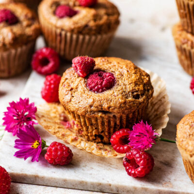 Several muffins with raspberries and pink bachelor's buttons around.