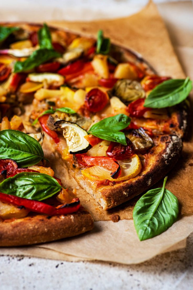 Vegetable topped pizza cut into triangles, side view.