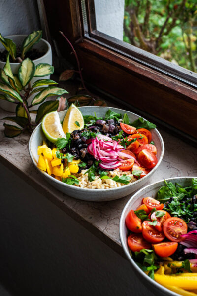 Two burrito bowls on a window ledge with a small plant in background.