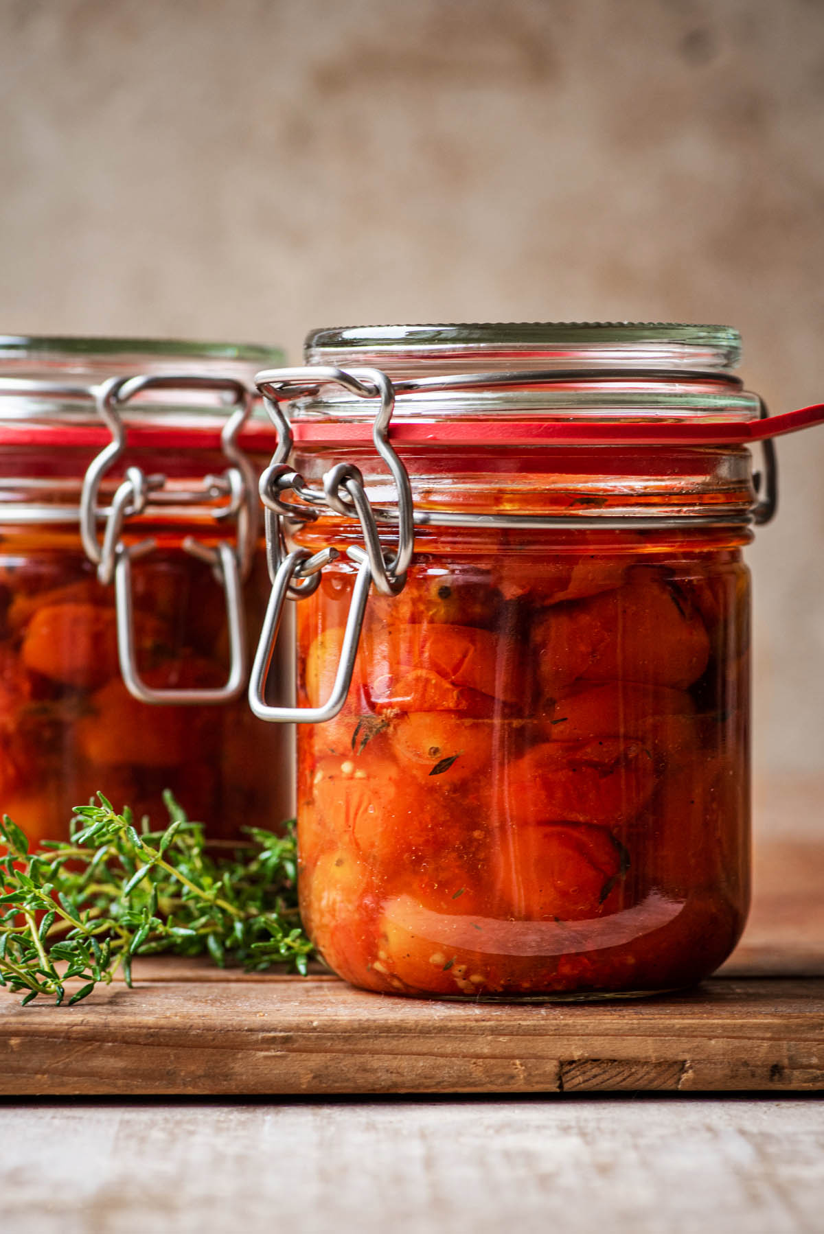 Two flip top jars filled with roasted tomatoes on a large wooden board.