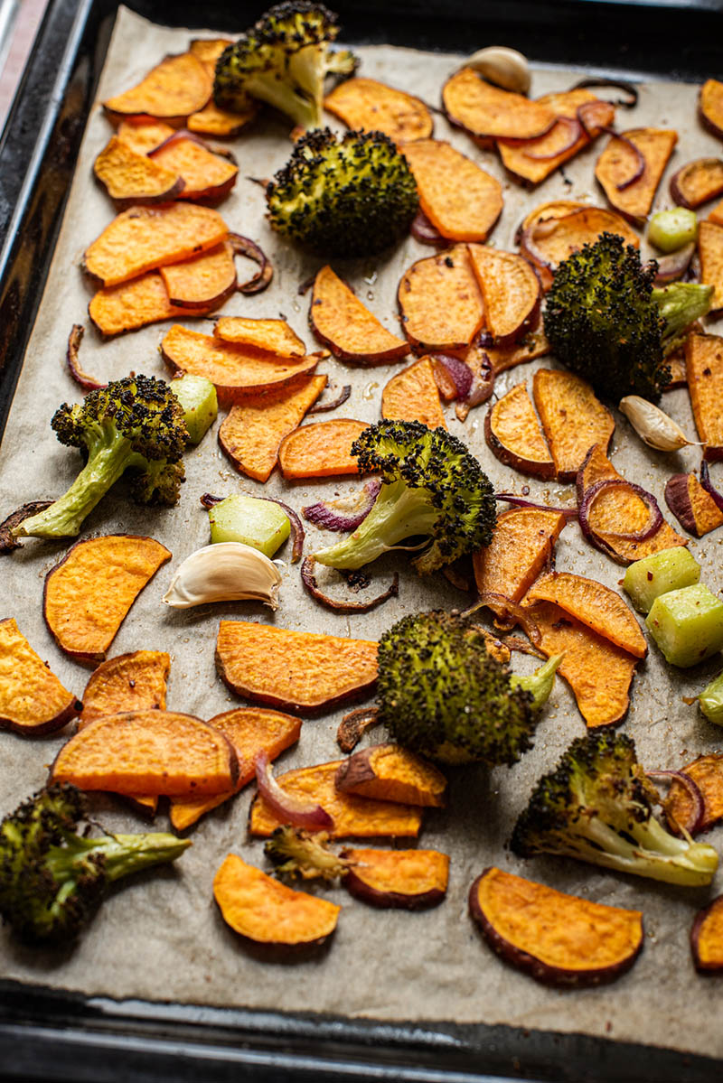 Roasted broccoli, sweet potato, red onion, and garlic on a sheet tray.