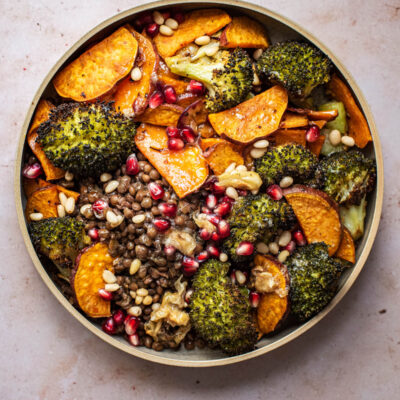 A broccoli and sweet potato lentil bowl with pomegranate seeds.