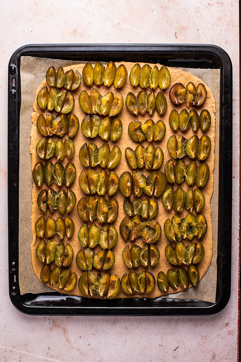Prune plums cut into attached quarters arranged on the dough.