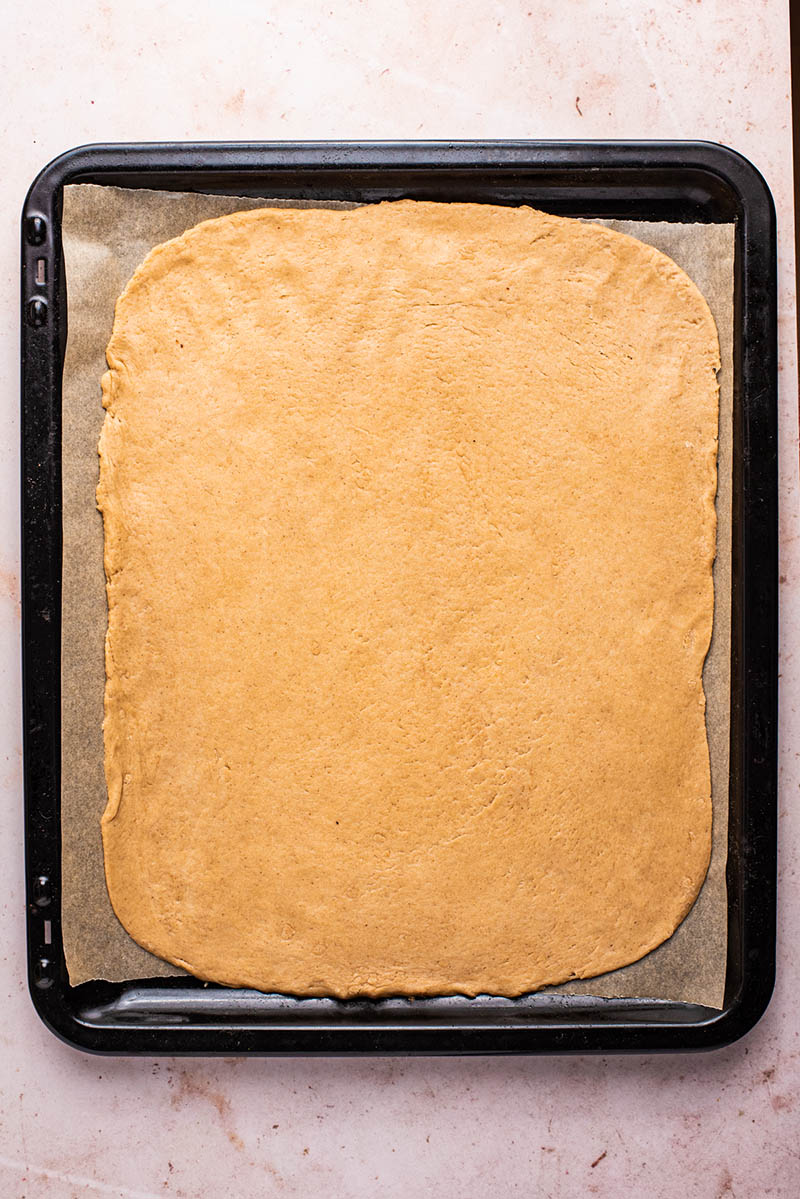 Dough rolled out onto a large baking sheet.