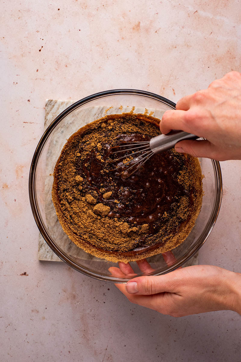 Whisking coconut sugar into the chocolate mixture.