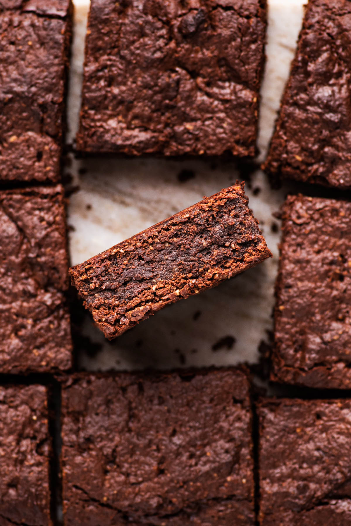Brownies cut into squares, with one facing up to see interior texture.