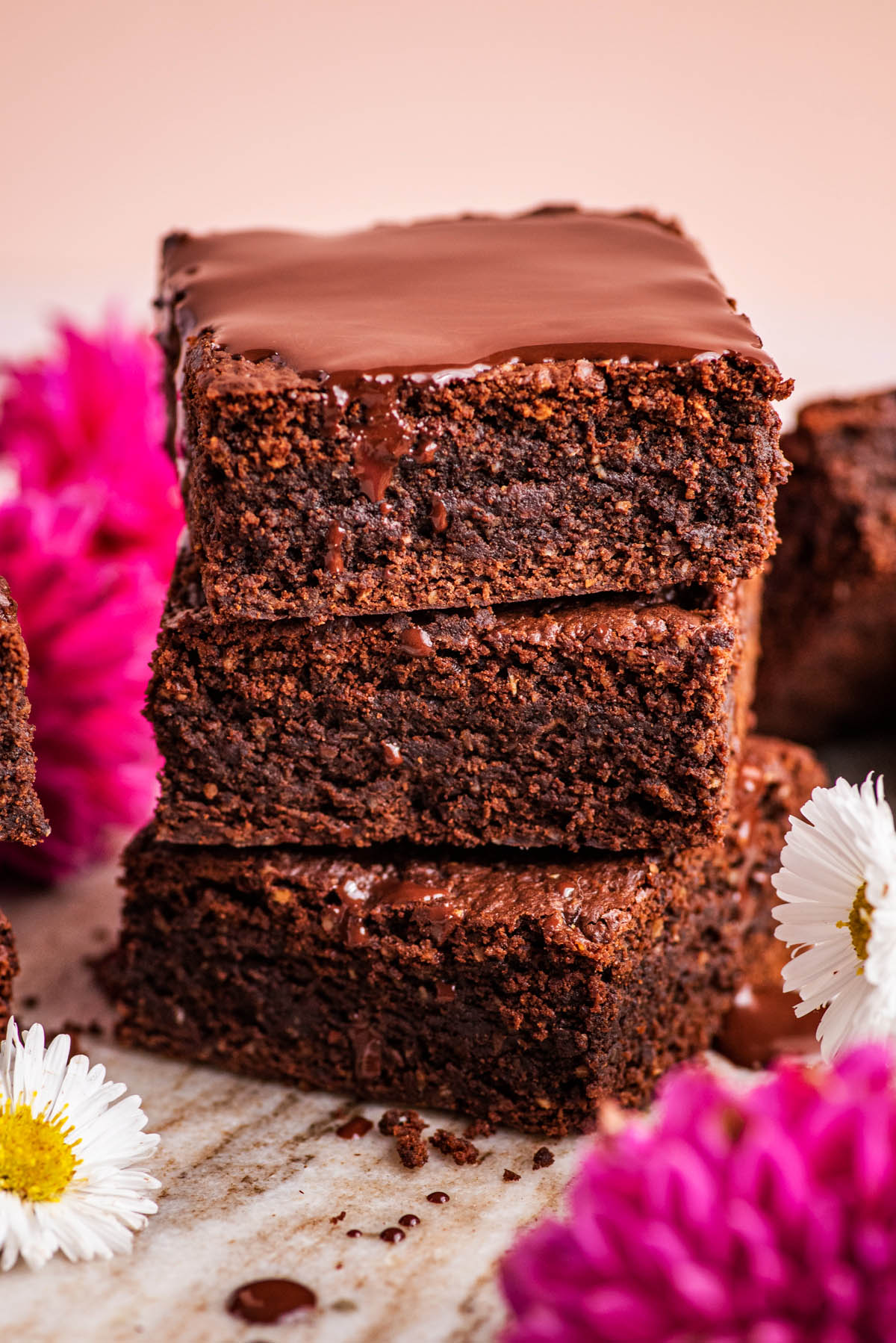 A stack of three brownies with melted chocolate and flowers.