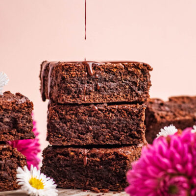 Chocolate drizzling onto a stack of three brownies.