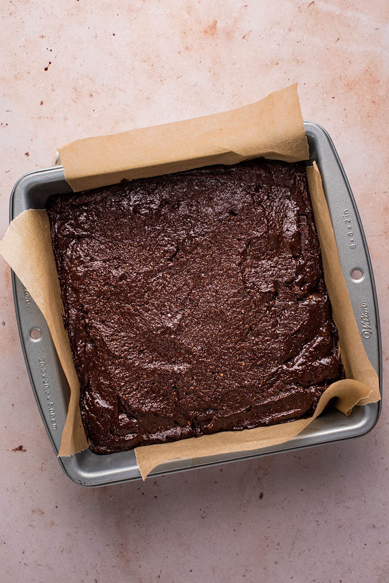 Unbaked brownie batter in a square tin lined with parchment paper.