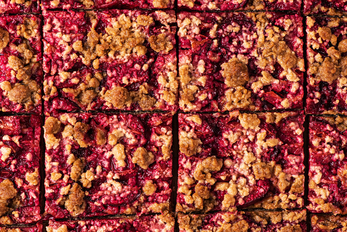 Close up of cut squares of streusel topped plum cake.