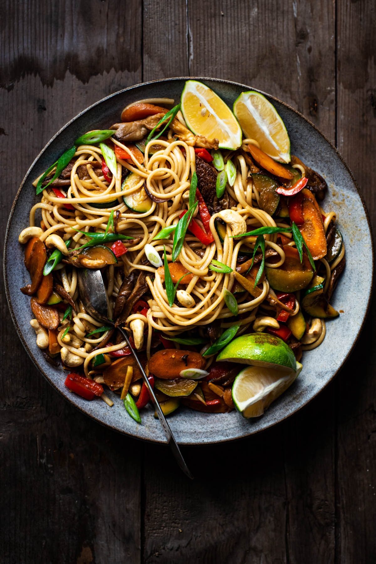 Vegetable soba noodle stir fry in a large bowl with lime wedges.