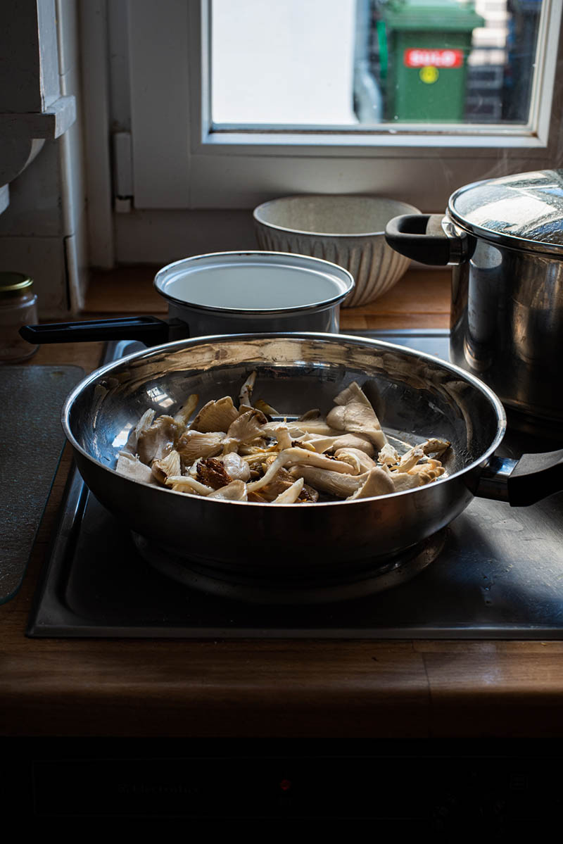 Oyster mushrooms in a large frying pan with olive oil.