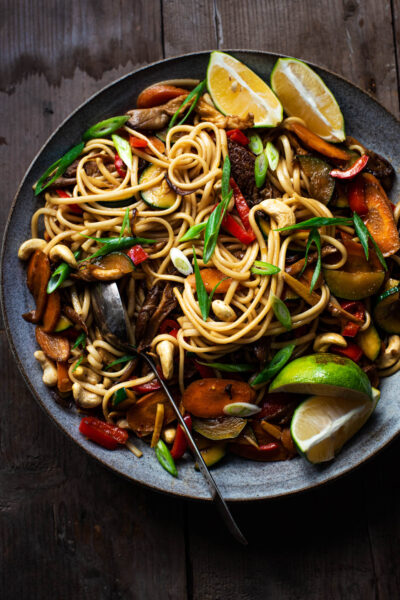 Close up of a stir fry noodle bowl with lime wedges.