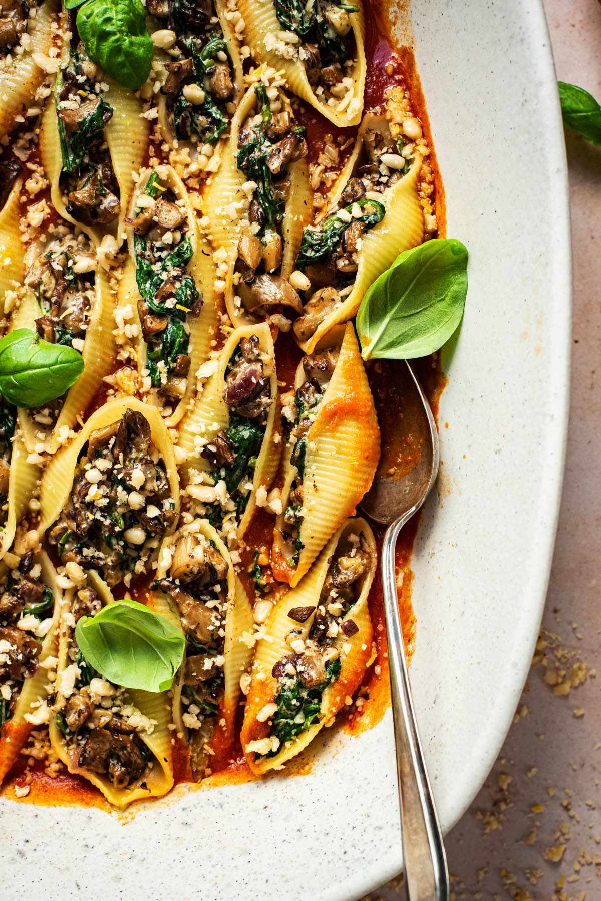 Close up of stuffed shells in tomato sauce with basil leaves.