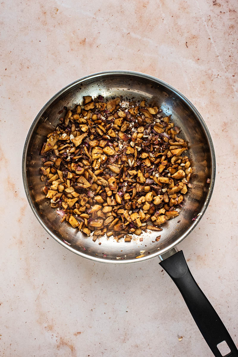 Onions, garlic, and mushrooms cooked in a large frying pan.