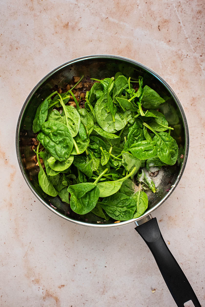 Fresh baby spinach added to the pan over the mushrooms.