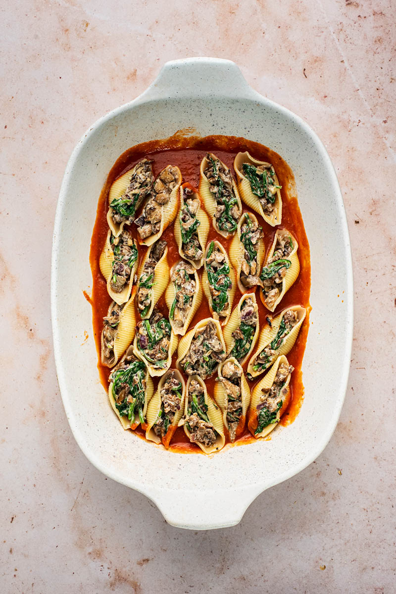 Pasta shells, filled with a mushroom mixture, in a large baking dish of tomato sauce.