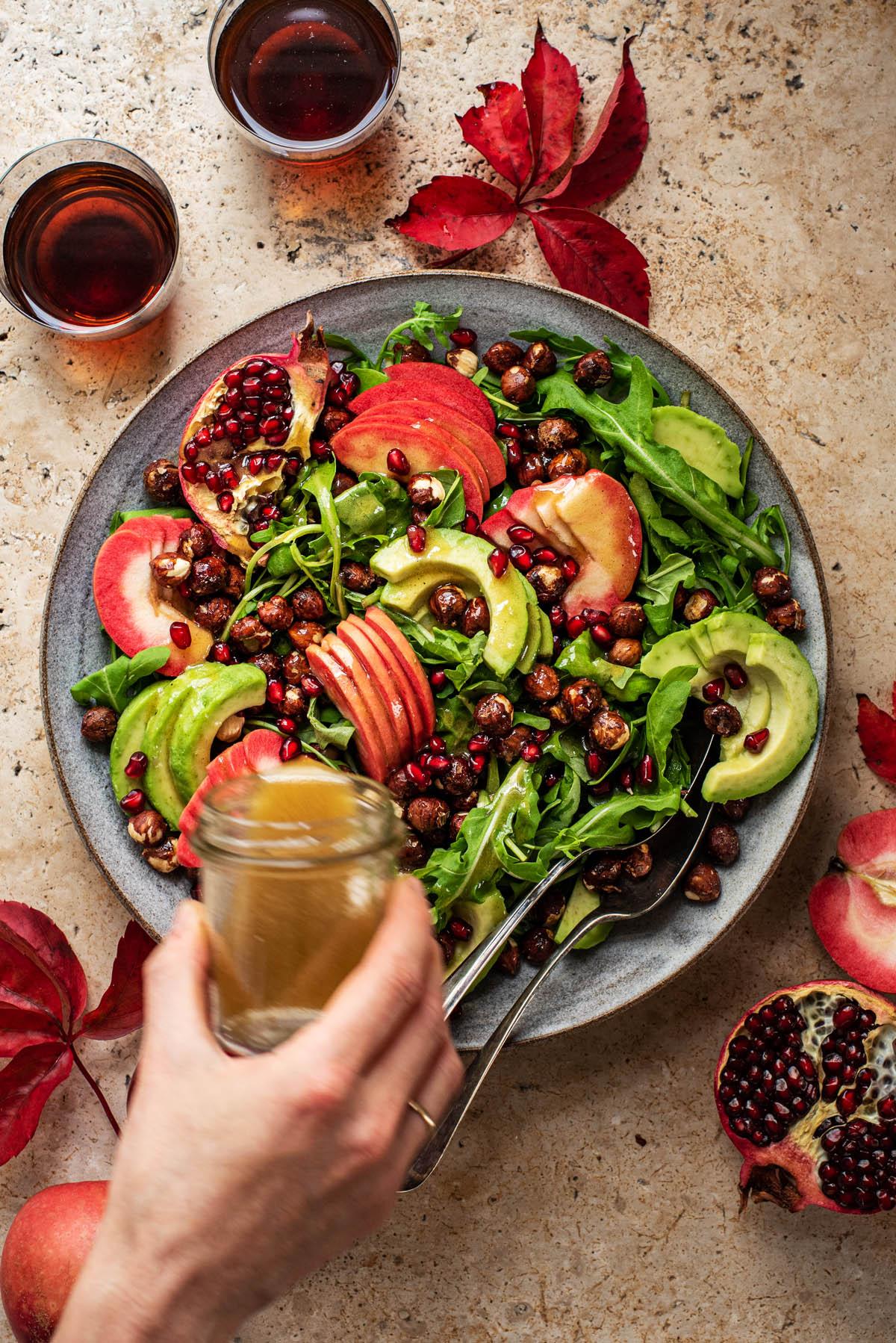 Pouring vinaigrette over an apple salad.