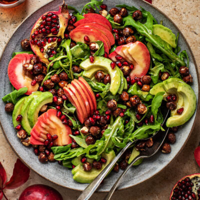 Large salad with sliced apples, avocado, nuts, and pomegranate.